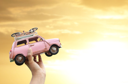 Hand holding classic mini model with yellow sky (travel concept) Stock Photo