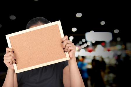 Asia girl holding empty cork board with blurred background