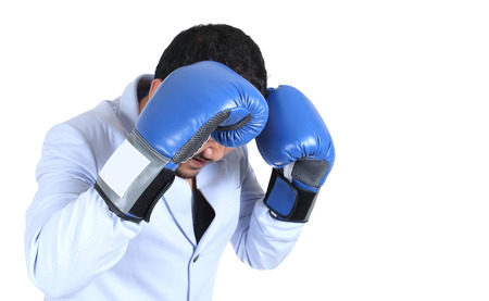 Businessman with boxing gloves guarding his face Stock Photo