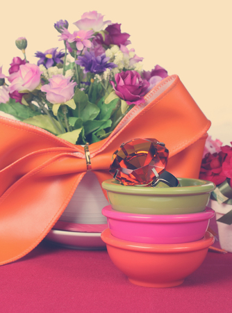 topaz ring in a bowl with colorful artificial flower Stock Photo