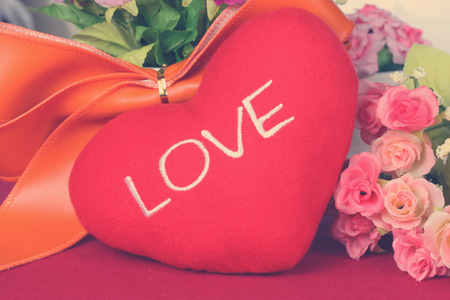 Red heart with colorful artificial flower - Close up Standard-Bild