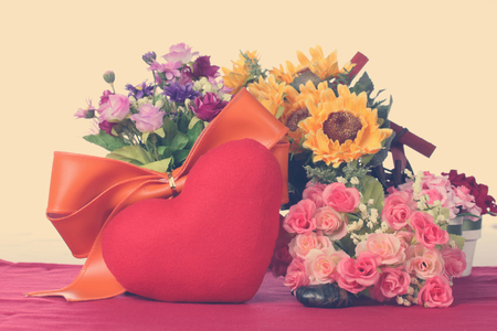 Red heart with colorful artificial flower Standard-Bild