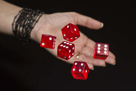 a hand throws red dice photo