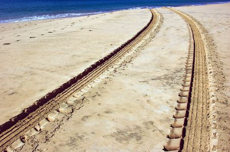 untitled key: Vehicle tracks in the sand on the beach. Stock Photo