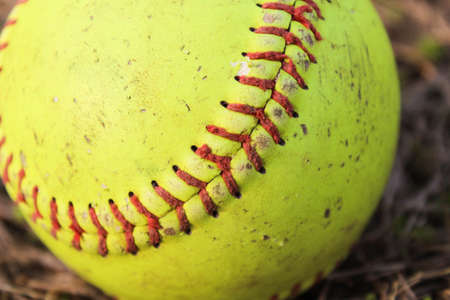 A worn softball found on the ground after a game in the park. Stok Fotoğraf