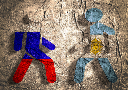 area of conflict: Image relative to politic relationships between Russia and Argentina. National flags on human icons. Concrete textured surface.