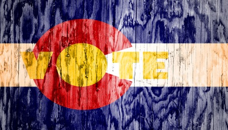 colorado flag: Vote word on Colorado flag background. Image relative to parliament, president and others elections in United States of America. Wood texture Stock Photo