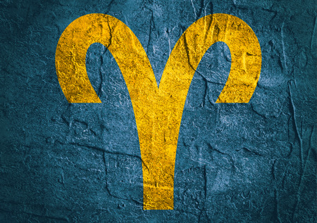 augury: Ram astrology sign. Yellow astrological symbol on concrete textured backdrop Stock Photo
