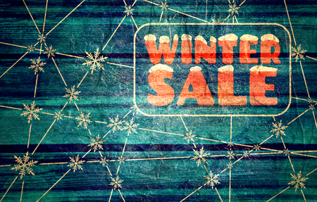 Winter sale inscription with snowflakes at the intersection of the lines. Retail business relative background. Wood texture