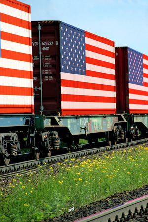 Train Freight transportation. Cargo transit. Summer Day. Container textured by flag of the USA Stock Photo