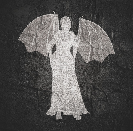 Sexy woman silhouette with bone wings standing in evening dress.