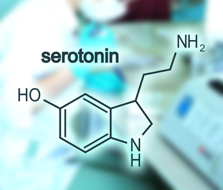 Chemical molecular formula hormone serotonin. Blurred backdrop with young female doctor Фото со стока