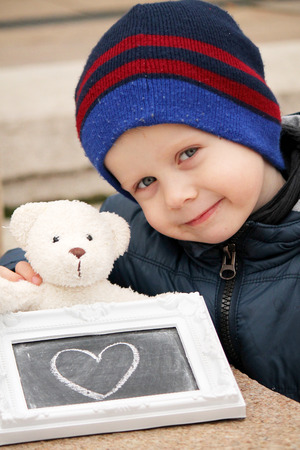 well being: boy with teddy bear and with drawing board Stock Photo