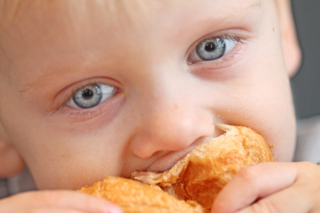 smudgy: Boy eating croissant Stock Photo