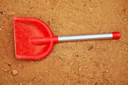 sandpit: Red spade in the sandpit