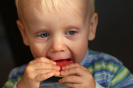 A boy eats a slice melon