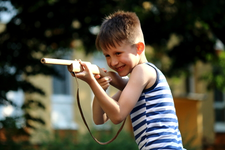 The boy plays with a wooden gun Standard-Bild