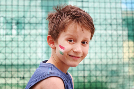 Smiling boy with his face hungarian tricolor tricolor