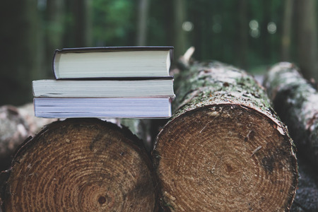 A stack of books lying on the logs,  save trees - read ebooks concept
