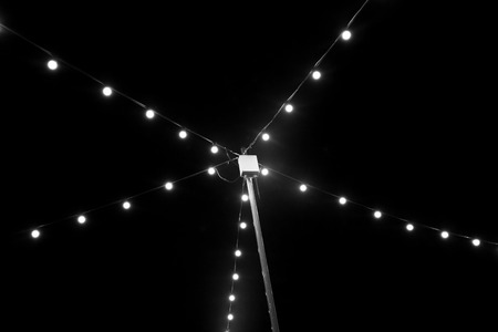 light bulbs on string wire hanging on pole against the background of darkness