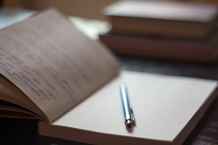 Open Notepad with handwritten notes with blue pen books in the background Stock Photo