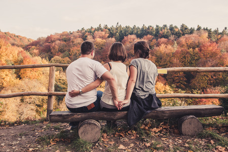 Three young beautiful people sit on a wooden bench and enjoy the autumn landscape, the concept of a love triangle and betrayal