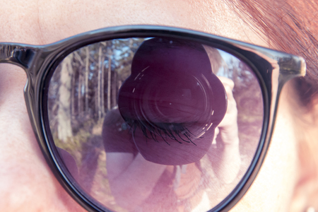 Lens of the camera with a blend which is photographed by a young guy is reflected in sunglasses put on a young girl, on the background of the forest Stock Photo