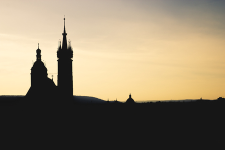 Black silhouette St. Mary Basilica in Krakow and panorama of the city center against a background of sunset and a fantastic beige amber sky
