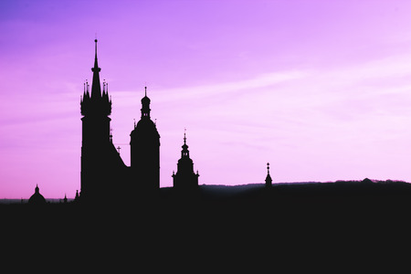 Black silhouette St Mary Basilica in Krakow and panorama of the city center against a background of sunset and a fantastic purple sky