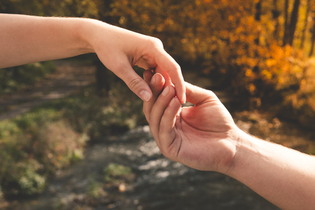 Mans hand gently holding the female against the background of the stream, concept of love and Valentine day Standard-Bild