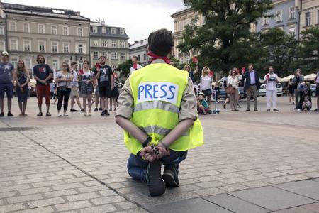 Cracovie, Pologne, 01 juin 2018, un homme solitaire dans le gilet de presse et les mains liées derrière le dos des manifestations contre la censure et l'interdiction de la liberté d'expression en arrière-plan, les gens montrent au gouvernement un carton rouge Éditoriale
