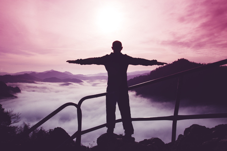 The silhouette of a single man with arms apart standing on top of a mountain against a surreal purple and red mountain landscape, the concept of success Foto de archivo