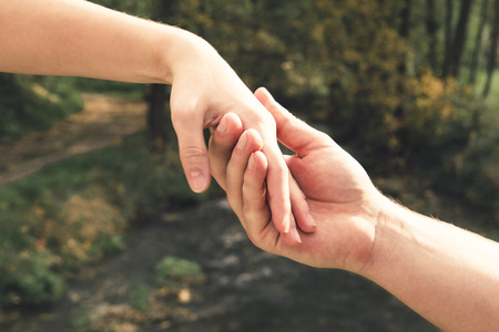 Mans hand gently holding the female against the background of the spring stream, concept of love and Valentine day Stockfoto - 110253492