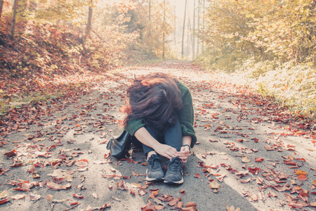 Brunette girl sitting on the ground with her head bowed to her knees in the autumn forest, autumn mood concept Stock Photo