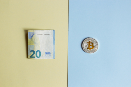 Bitcoins and EURO on a pastel background, the concept of confrontation between cryptocurrency and paper money