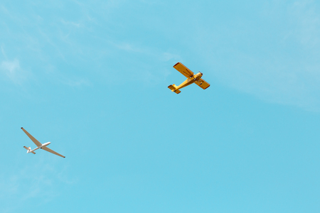 A small yellow plane and glider flying across the blue sky Stock fotó