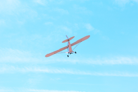 Small single-engine old vintage plane flying against the blue sky