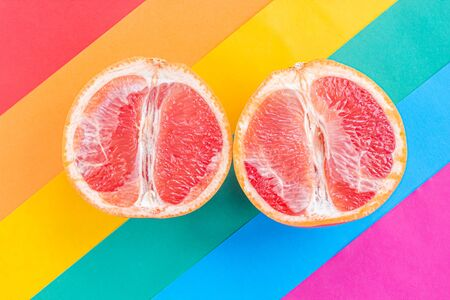 LGBT love concept, two grapefruits lie on the rainbow flag, symbol of female love Stock Photo