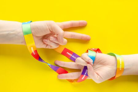 LGBT symbol diversity and inclusion - two hands wrapped in rainbow ribbon show V - symbol of victory, concept communities and equality all people