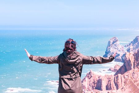 A girl with outstretched arms enjoys a stunning view of the ocean and rocks.
