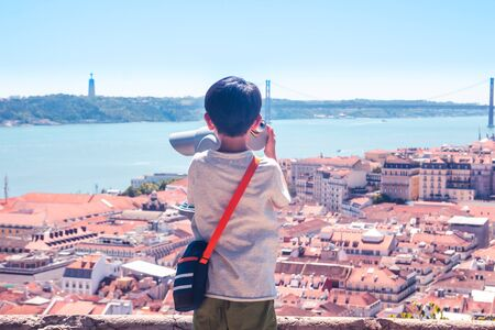 Little boy playing with a binoscope on the observation deck overlooking the old town