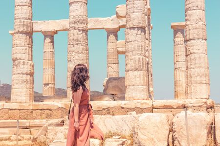 A young girl in a brown summer dress looking at the ancient temple of Poseidon on the Cape Sounion, closeup