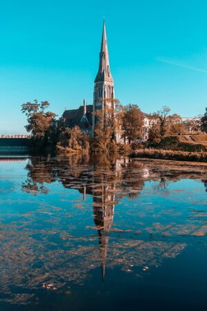St Albans Church reflected in the water in late autumn against the blue sky