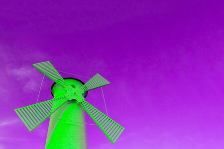 A bright green windmill against a purple sky, a concept of creativity and surreal architecture