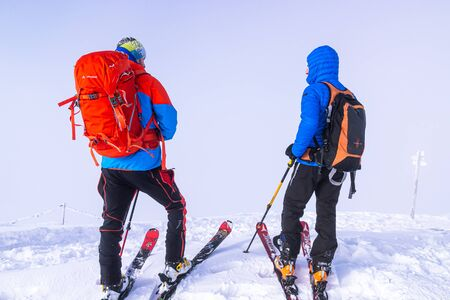Zakopane, Tatra mountains, Poland - December 16, 2019 Two mountain skiers travelers with large backpacks are preparing to move down the mountain