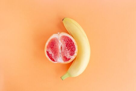 Yellow banana and grapefruit on a pastel orange background, marital love concept