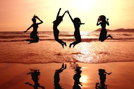 silueta de amigos saltando en puesta de sol Foto de archivo