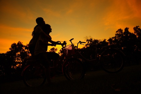 happy couple embrace on bicycle in the park photo