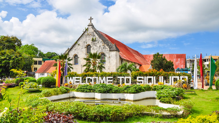 City of Siquijor Welcome Sign, behind which is the Spanish colonial era church Saint Francis de Assisi - Siquijor, Philippines