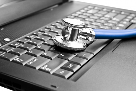 health technology: Stethoscope on black laptop computer